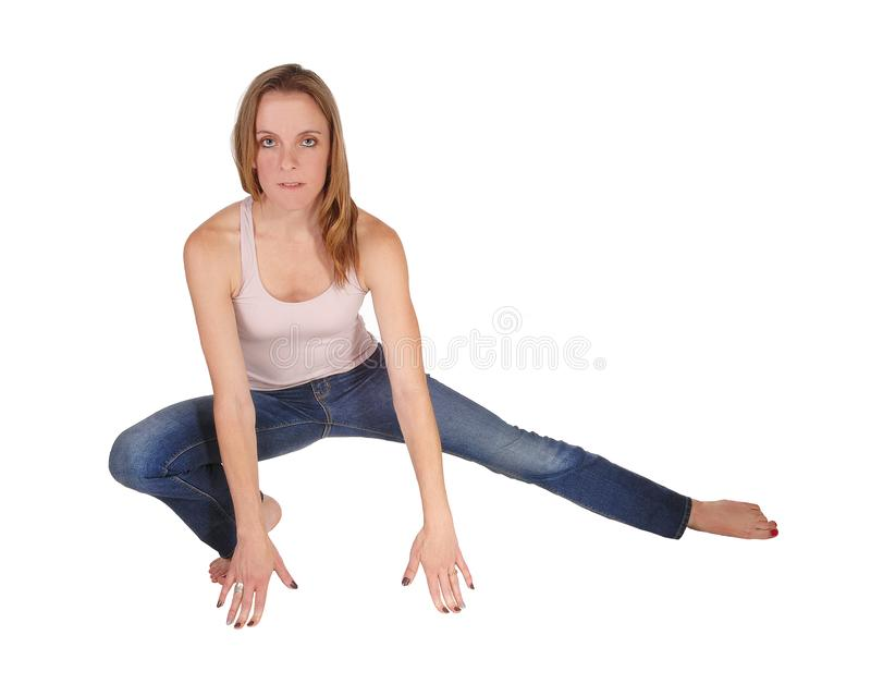 Young woman crouching on the floor. A slim young woman in jeans and a pink top crouching on the floor.bare feet, looking serious, isolated for white background royalty free stock photography