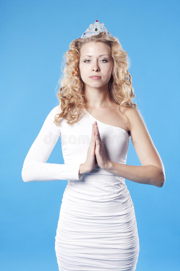 Young woman with crown praying royalty free stock photography