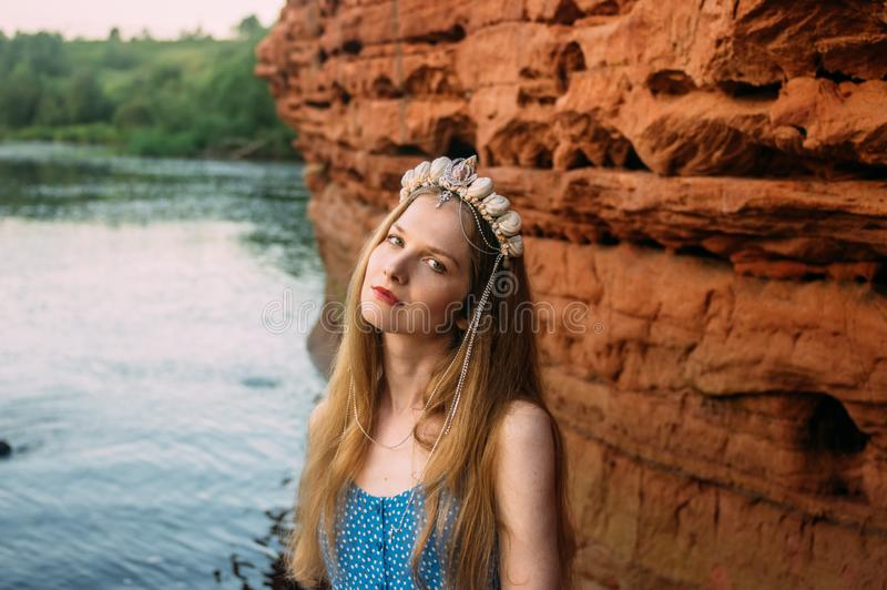 Young woman in crown from shells staying near red sand wall. Near river royalty free stock photos