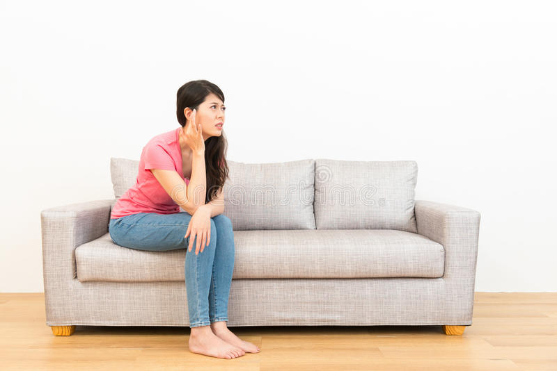 Young woman crushed ear painful position. Sitting on couch looked at white background with wood floor at home in living room stock image