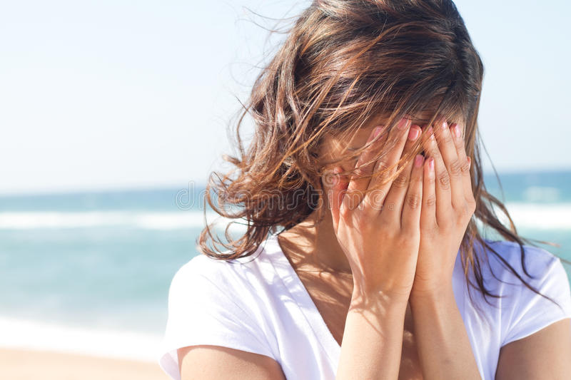 Young woman crying. A young woman crying with her face in her hands on the beach royalty free stock photography