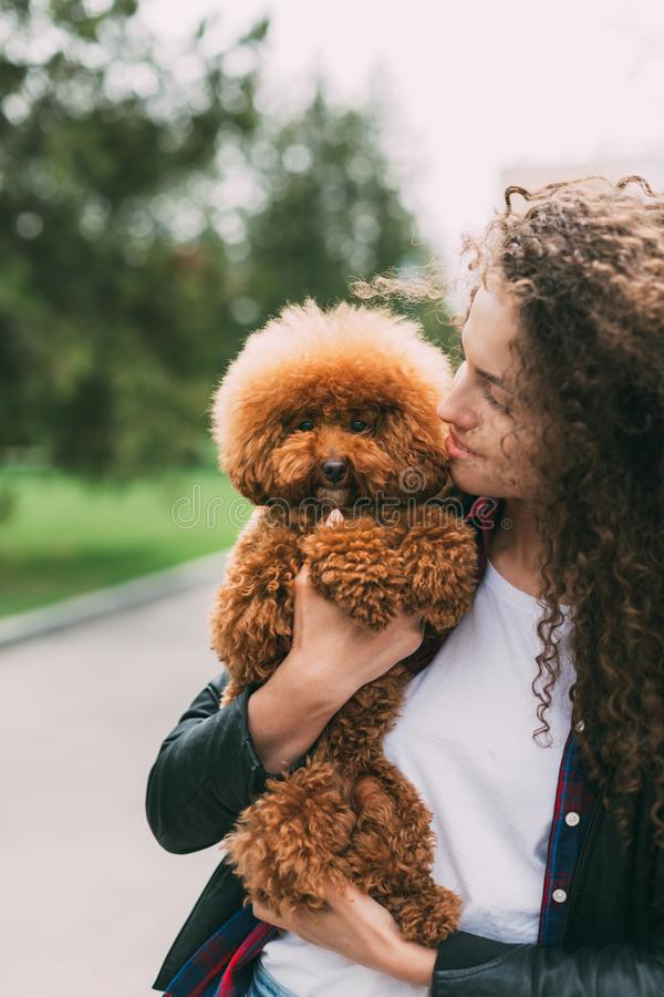 Young woman cuddling with her cute little poodle royalty free stock photography