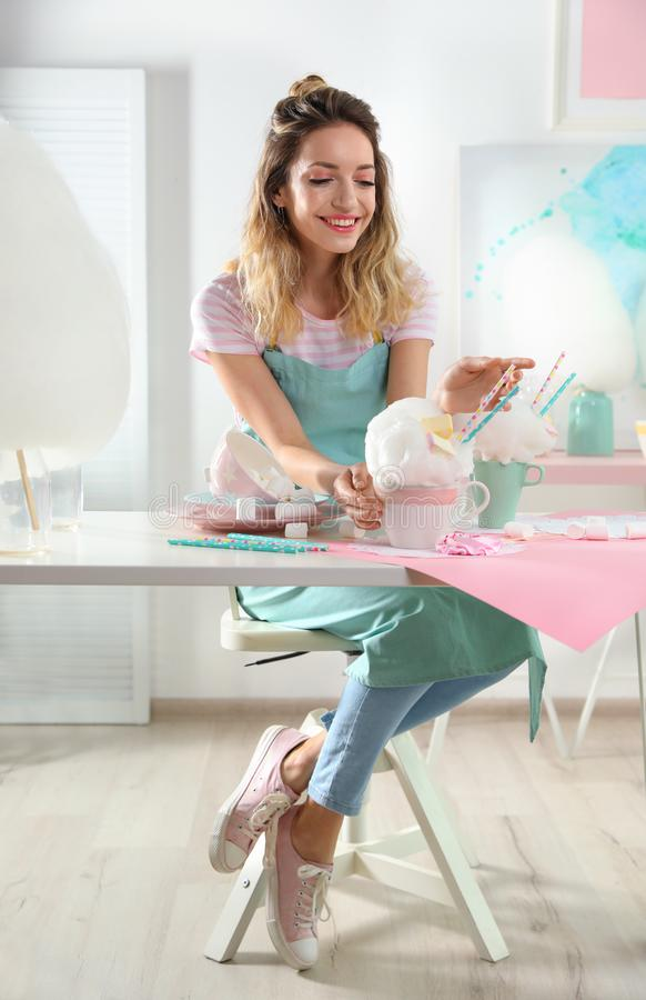 Young woman with cup of cotton candy dessert at table royalty free stock photo