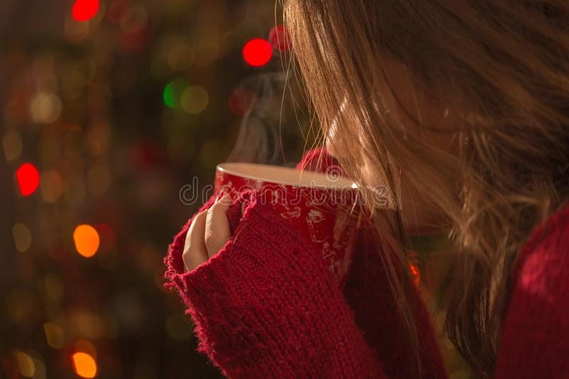 Young woman with cup of hot chocolate or tea or coffee in front of Christmas tree. Relaxing and christmas concept. royalty free stock images