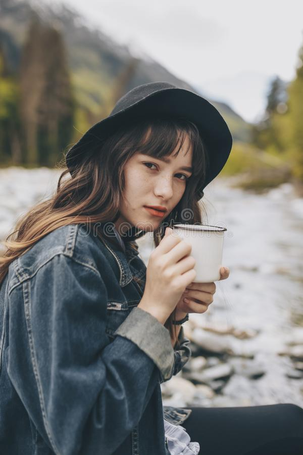 Young woman with cup outdoor portrait in soft sunny daylight royalty free stock photography