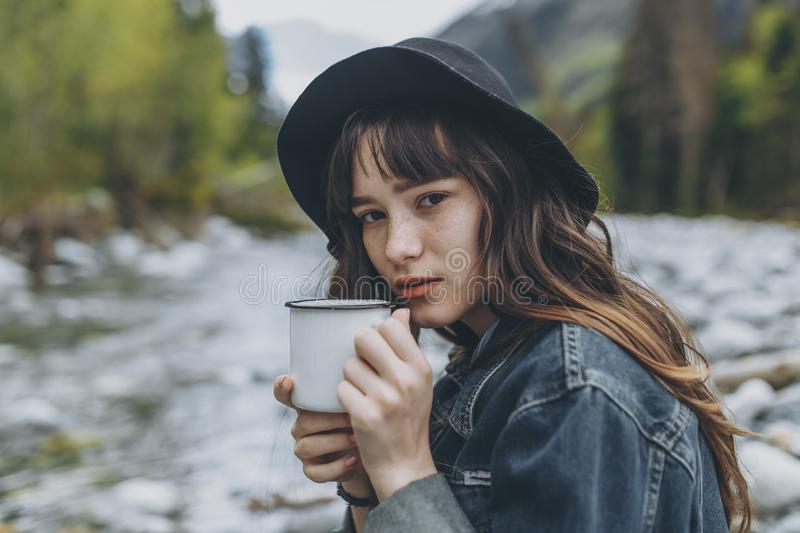 Young woman with cup outdoor portrait in soft sunny daylight royalty free stock photo