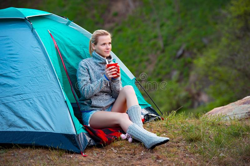 Young woman with a cup of tea near a tent against green forest b royalty free stock images