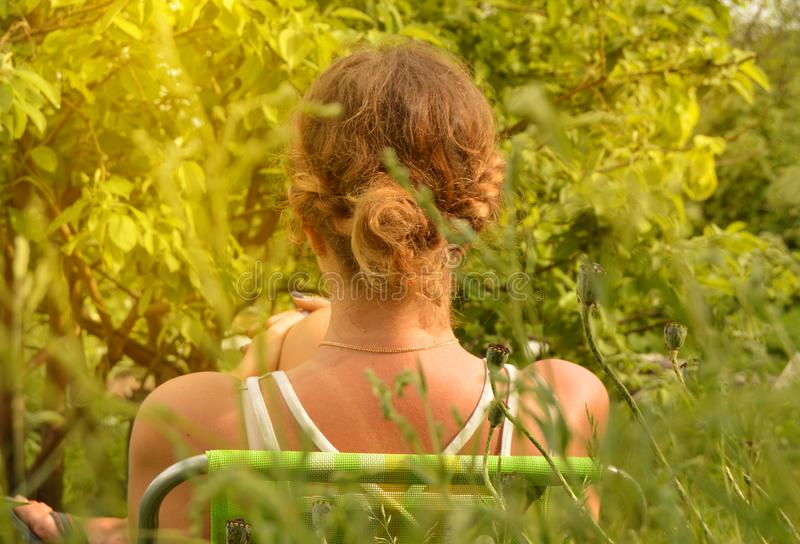 A young woman with curly blonde hair in a white t-shirt resting in a chair in the garden, vertical shot royalty free stock image