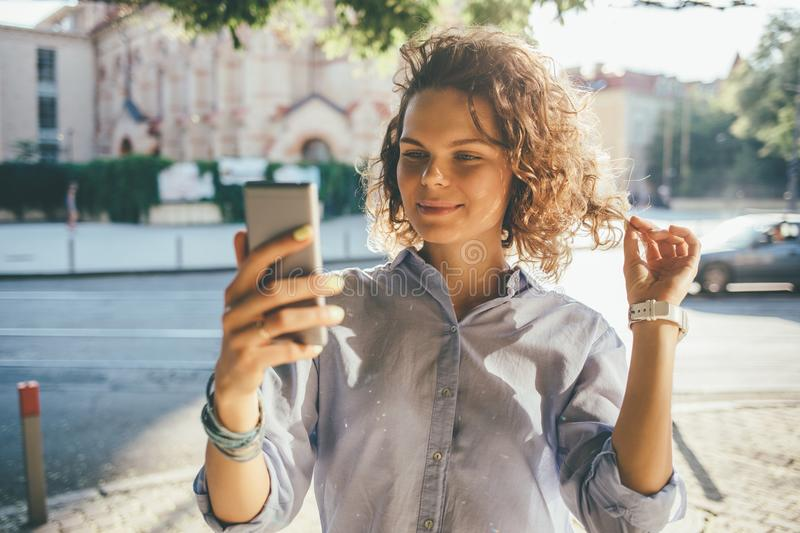 Young woman with curly hair making selfie stock photo