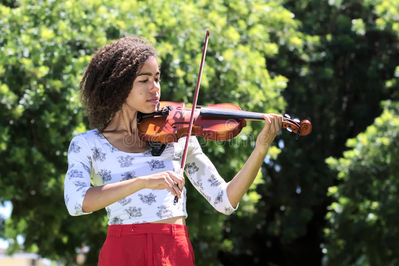 Young woman with curly hair playing violin outdoors. Half length portrait of a young African American woman wearing a white patterned blouse, red skirt, and royalty free stock images