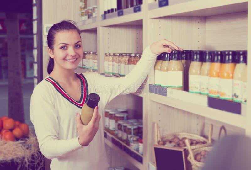 Young woman customer examining various juices stock photo