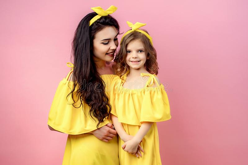 Young woman with cute child posing in yellow dresses royalty free stock photography