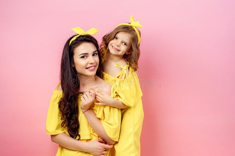 Young woman with cute child posing in yellow dresses stock images