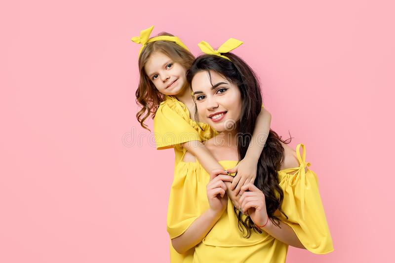 Young woman with cute child posing in yellow dresses royalty free stock images