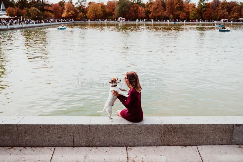 young woman and cute dog by the lake in an urban park. Love for animals concept. Retiro park Madrid royalty free stock photo