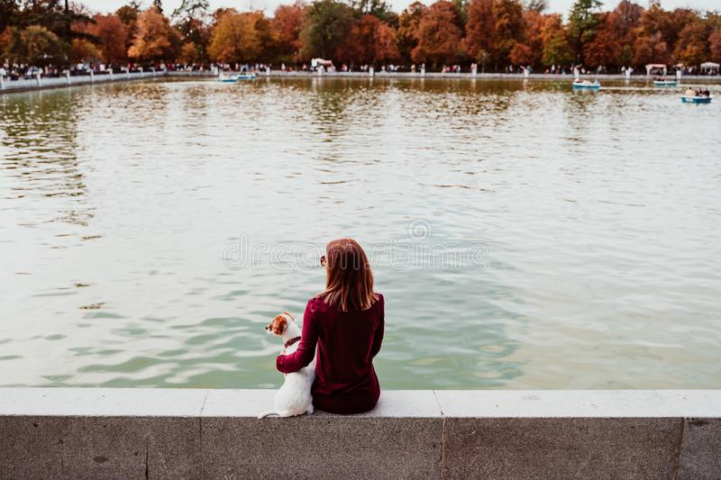 young woman and cute dog by the lake in an urban park. Love for animals concept. Retiro park Madrid royalty free stock images