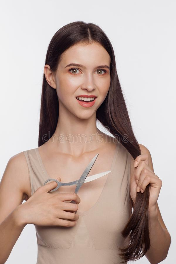 Young woman cuts off her hair by scissors. Beautiful young woman cuts off her hair by scissors royalty free stock image