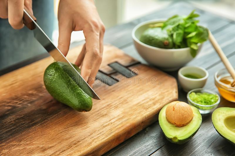 Young woman cutting avocado for nourishing mask at table royalty free stock image