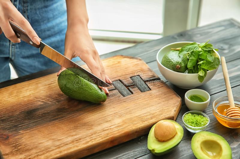 Young woman cutting avocado for nourishing mask at table royalty free stock photos