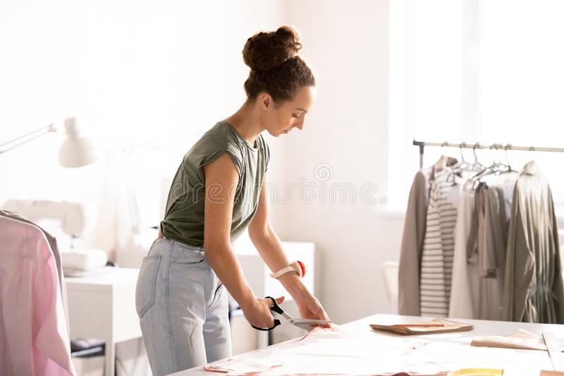 Cutting pattern. Young woman cutting fabric by edge of paper pattern while making new item for seasonal fashion collection royalty free stock photography