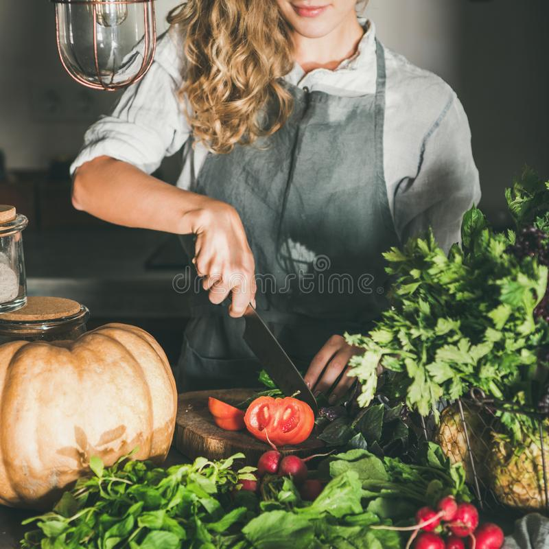 Young woman cutting herbs and vegetables for cooking, square crop stock photos