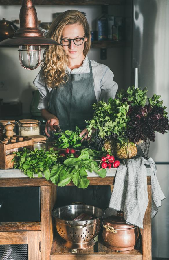 Young woman cutting herbs and vegetables in kitchen stock image