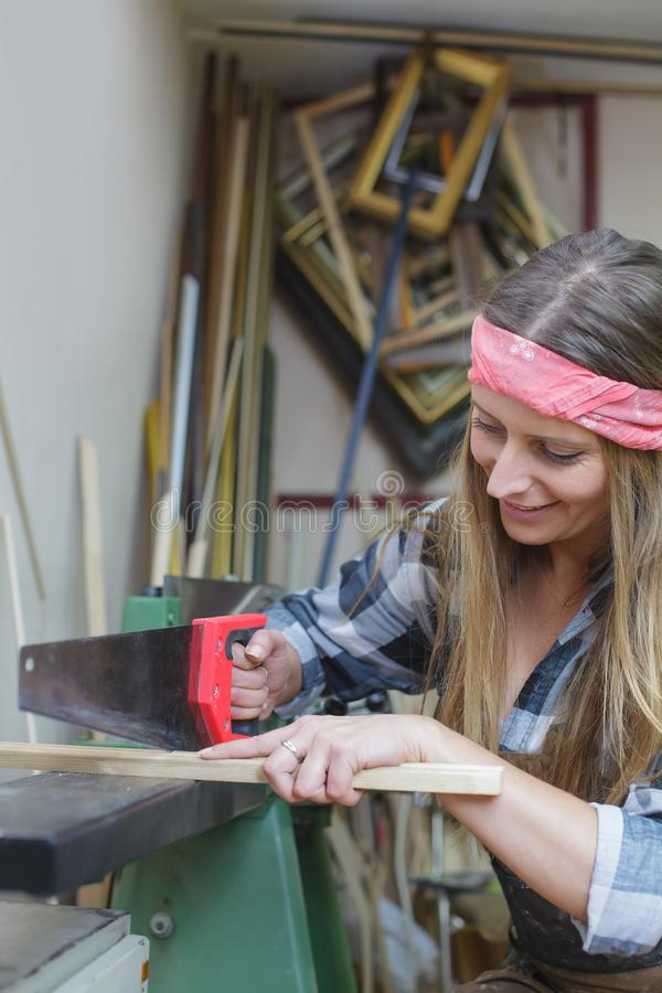 Young woman cutting wooden frame. Young woman sawing wooden slat royalty free stock photo