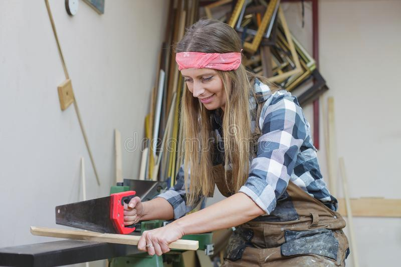 Young woman cutting wooden slat. Young woman sawing wooden slat stock image