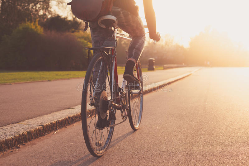 Young woman cycling in the park at sunset royalty free stock photos