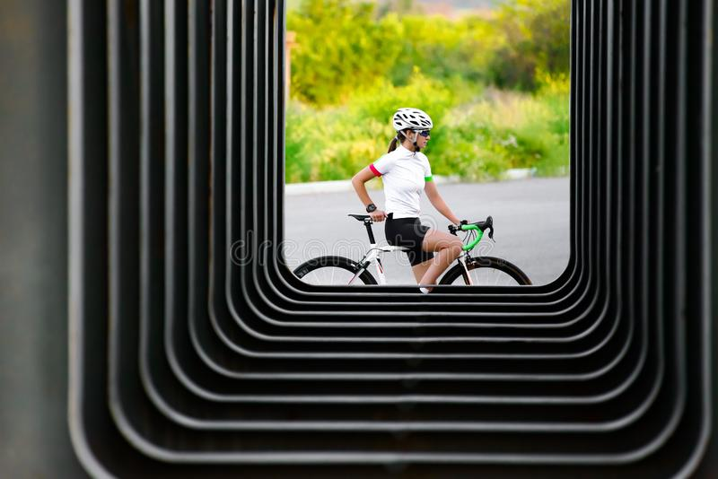 Young Woman Cyclist Resting with Bicycle near Urban Constructions in the City. Healthy Lifestyle and Sport Concept. Young Woman Cyclist Resting with Road Bicycle royalty free stock image