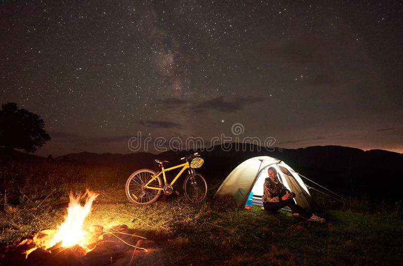 Woman resting at night camping near campfire, tourist tent, bicycle under evening sky full of stars. Young woman cyclist resting at night camping near burning royalty free stock photos