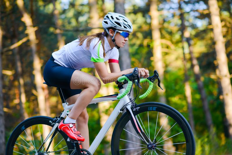 Young Woman Cyclist Riding Road Bicycle on the Free Road in the Forest at Hot Summer Day. Healthy Lifestyle Concept. Young Woman Cyclist Riding Road Bicycle on royalty free stock photos