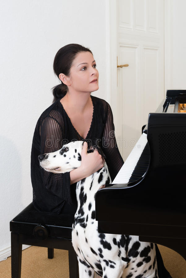 Young woman with dalmatian dog. Sitting by by grand piano royalty free stock image