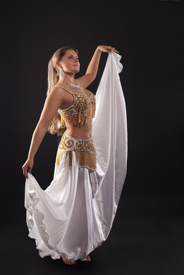 Young woman dance in dark - white arabian costume