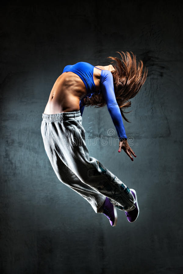Young woman dancer jumping. On wall background stock photography