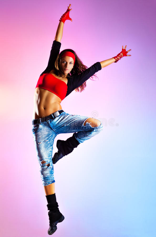 Young woman dancer jumping. On blue and pink background royalty free stock photo