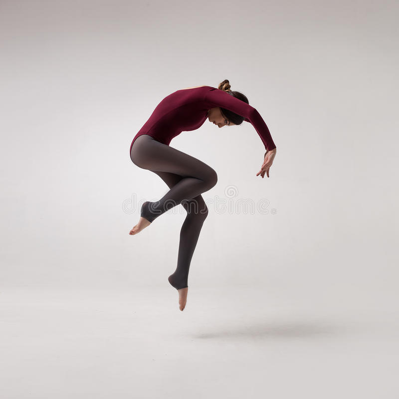 Young woman dancer in maroon swimsuit jumping. Young beautiful woman dancer with long brown hair wearing maroon swimsuit jumping on a light grey studio royalty free stock photo