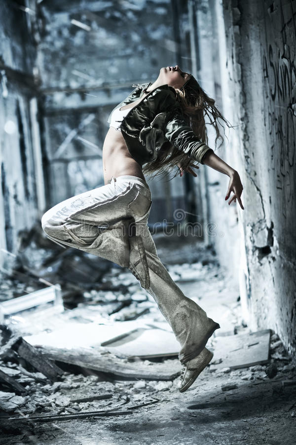Young woman dancing. On industrial background