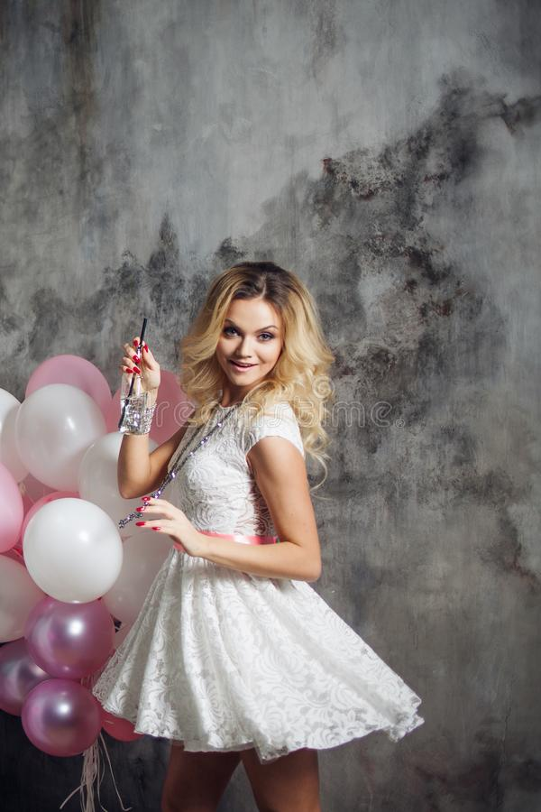 Young woman dancing and drinking soda. Portrait of a beautiful glamorous blonde, with a bottle of drink and balloons. stock photography