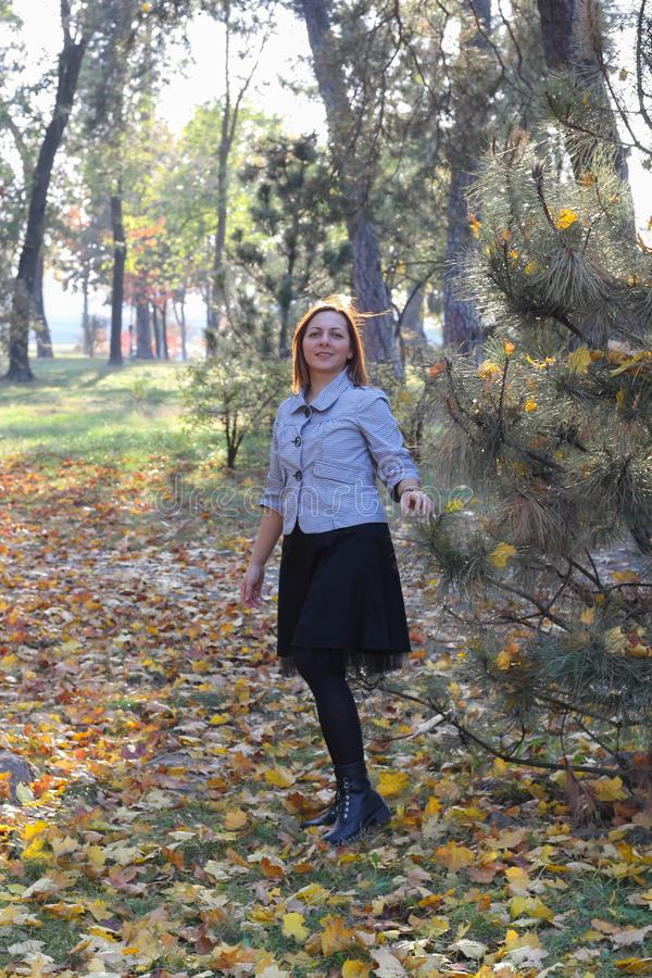 Young woman is dancing on a road. It is fall, the background shows orange trees. She got a nice style, fashionable stock images
