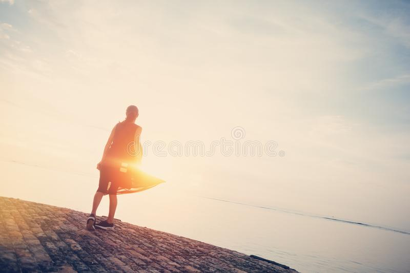Young woman dancing at sunrise near ocean stock photography