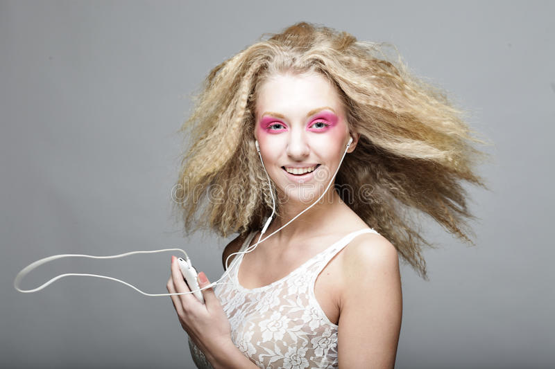Young woman dancing to music on her headphones stock image