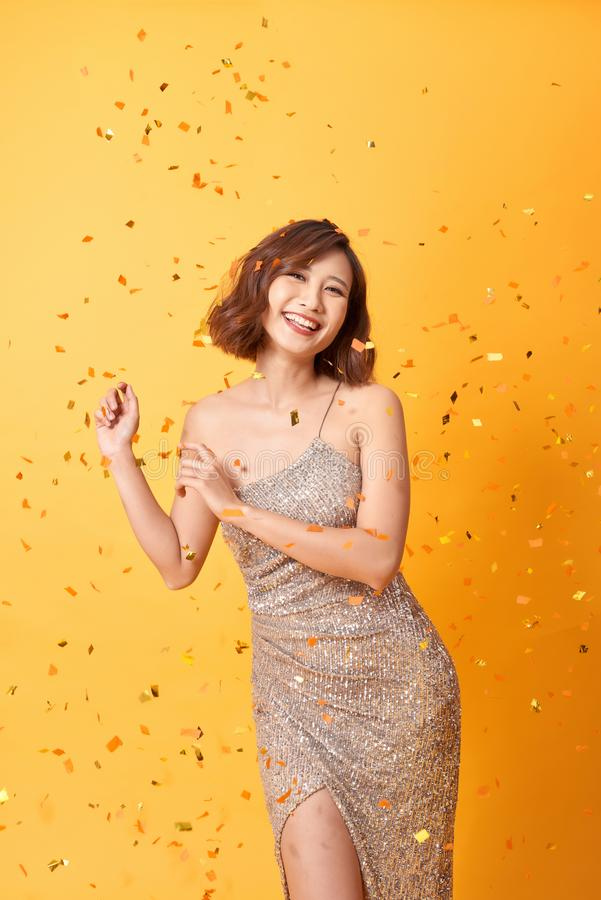 Young woman dancing under confetti at home, celebrating birthday.  stock images