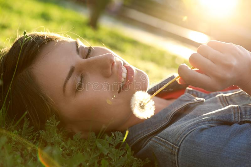 Young woman with dandelion in park. Allergy free concept stock images