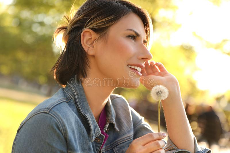 Young woman with dandelion in park. Allergy free concept stock photos
