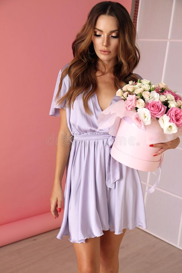 Young woman with dark curly hair in elegant outfit with flowers stock photo