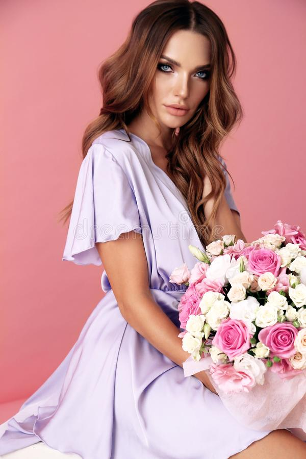 Young woman with dark curly hair in elegant outfit with flowersflowers royalty free stock photos