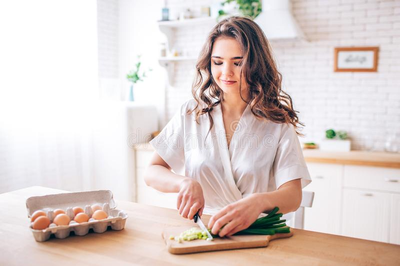 Young woman with dark hair standing in kitchen and cutting green onion. Eggs besides. Morning daylight. Alone in kitchen royalty free stock photography
