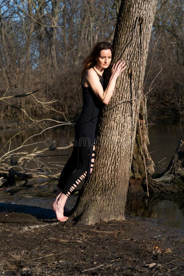 Young woman with dark long hair in black robes is leaning against the tree in the middle of the forest. Back to Nature concept.  royalty free stock photo