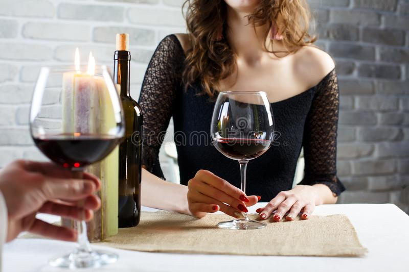 Young woman drinking red wine on a date in a restaurant royalty free stock photos